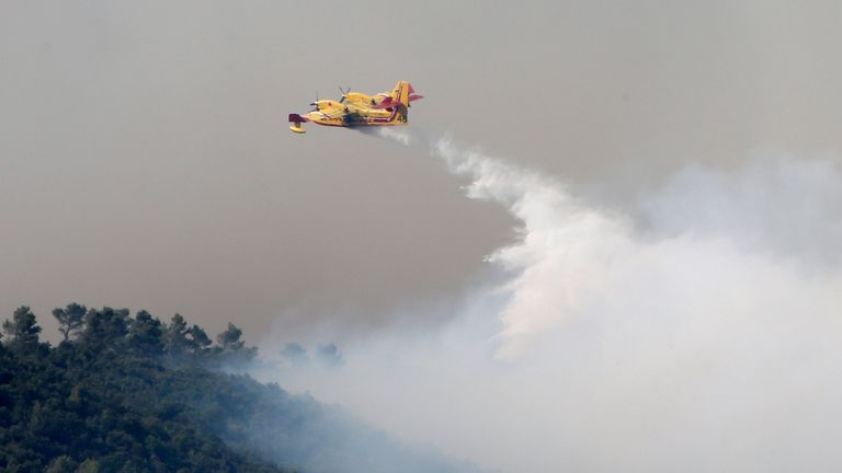 Smoke fills the sky as a Canadair firefighting plane releases water to extinguish a wildfire near Seillons, in the Var department
