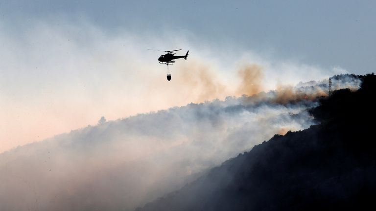 A firefighting helicopter flies above smoke from a wildfire which burns in Peyrolles, France