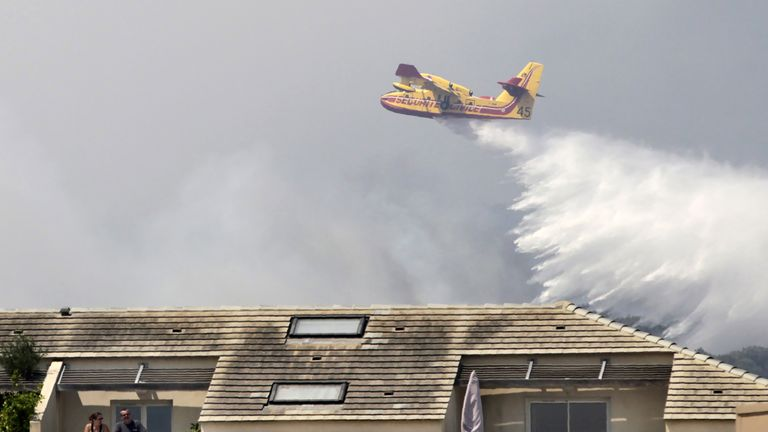 People stand outside on a balcony as a Canadair aircraft drops water over a fire  near Biguglia, on the French Mediterranean island of Corsica