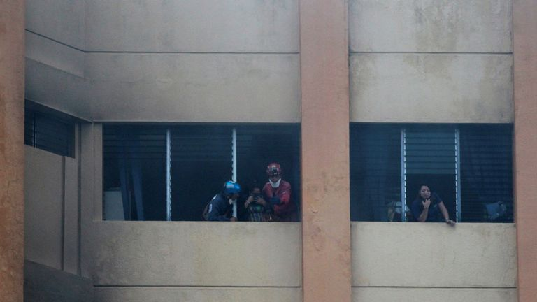 Workers are helped by rescuers at the ministry of treasury building during a blaze in San Salvador, El Salvador, July 7, 2017