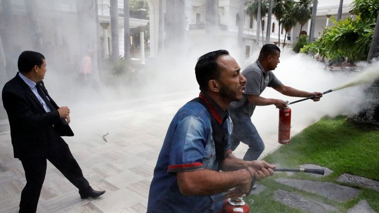 People use fire extinguishers during clashes with government supporters outside the National Assembly