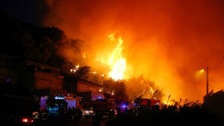 Firefighters work to put out a fire in Biguglia, on the French Mediterranean island of Corsica