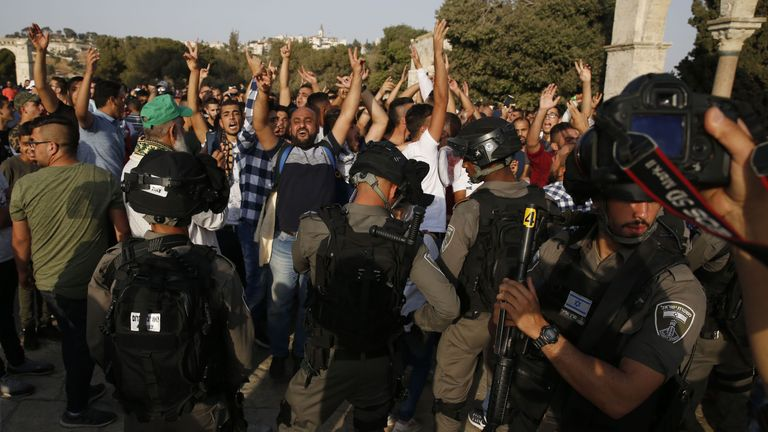 Palestinians flash the victory gesture and shout slogans in front of Israeli security forces