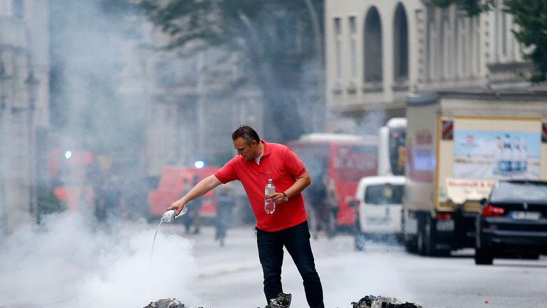 A man pours water over a burnt rubbish bin