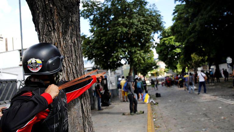 A demonstrator uses a slingshot