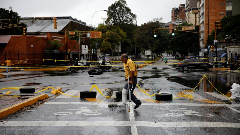 A pedestrian walks past a barricade