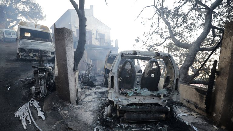 Vehicles that were destroyed by a burning wildfire near a damaged home in Carros, near Nice