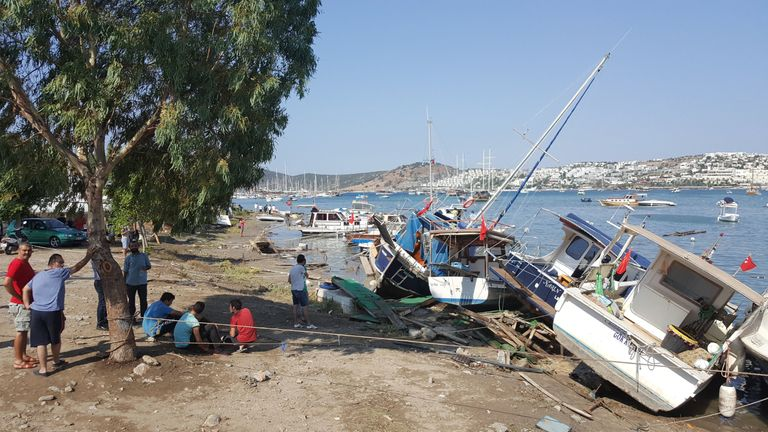 People stand next to damaged boats after an earthquake and a tsunami in the resort town of Gumbet