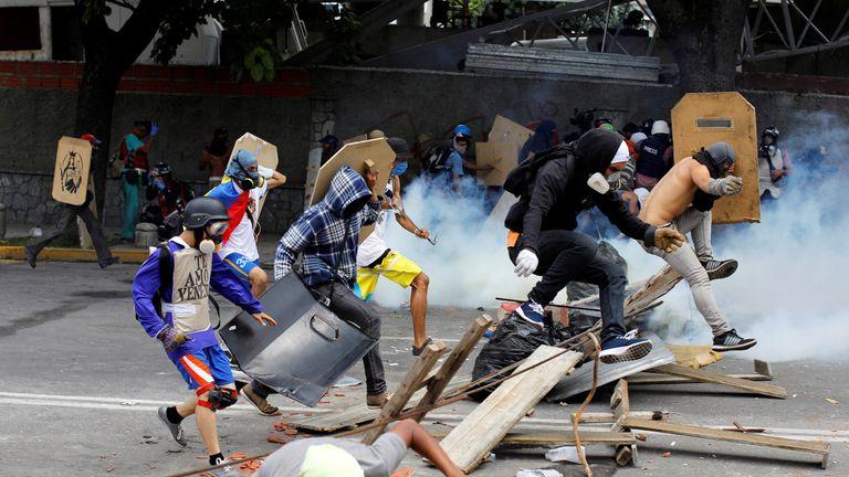 Demonstrators run away at a rally against Venezuelan President Nicolas Maduro's government in Caracas