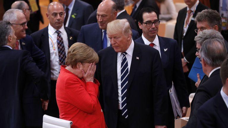German Chancellor Angela Merkel reacts next to US President Donald Trump