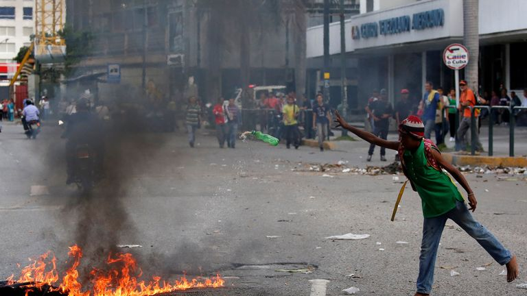 A barefoot man throws a bottle on a barricade