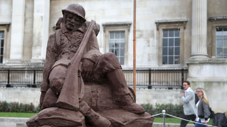 Artificial rain falls on the 'Mud Soldier' statue, which is sculpted from sand and mud from Passchendaele, on the North Terrace of Trafalgar Square