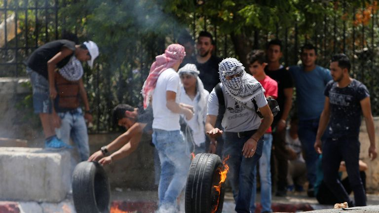 A Palestinian protester moves a burning tire as he takes cover during clashes