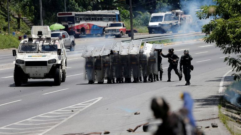 A demonstrator hurls rocks at security forces during clashes at a rally against Venezuelan President Nicolas Maduro's government in Caracas