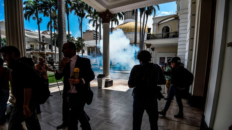 Journalists react as supporters of Venezuelan President Nicolas Maduro storm into the National Assembly building