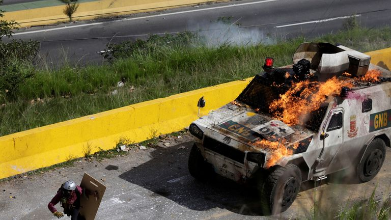 An armoured vehicle on fire during clashes with demonstrators