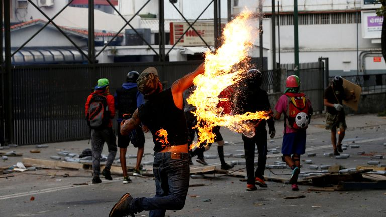 A demonstrator throws a petrol bomb