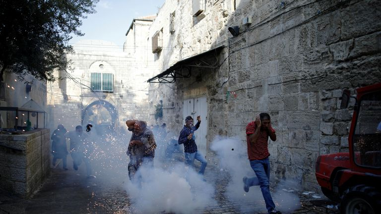 Palestinians react as a stun grenade explodes in a street in Jerusalem's Old City