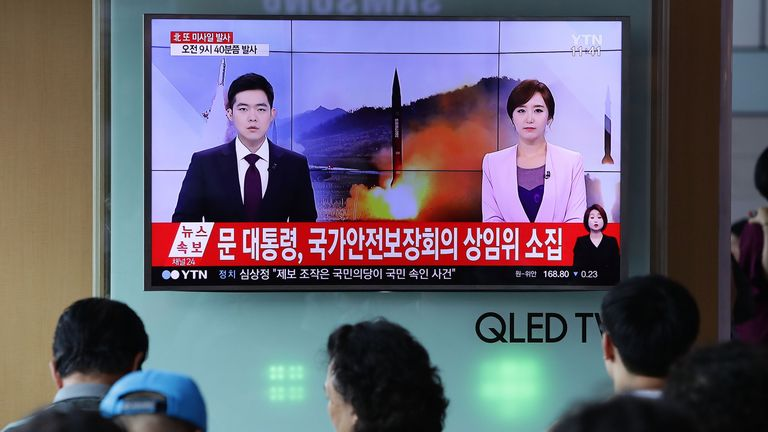People watch South Korean TV reports of the ICBM launch