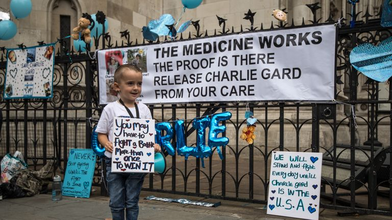 A young boy holds a placard given to him by his mother as supporters of of terminally ill baby Charlie Gard protest outside the High Court after the verdict was announced on July 24, 2017