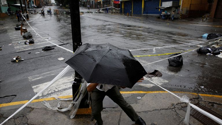 A pedestrian walks through a barricade