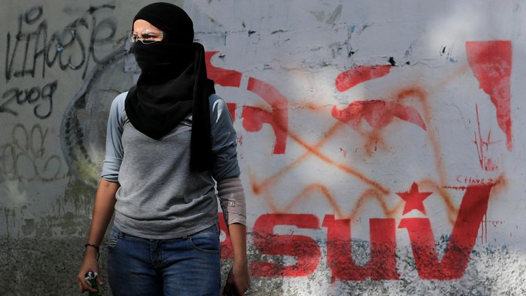 A demonstrator stands next to a graffiti depicting the eyes of Venezuela's late President Hugo Chavez as she holds Molotov cocktails