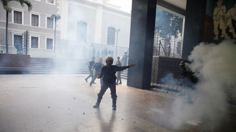 A member of the National Guard gestures as government supporters (not pictured) throw firecrackers at the National Assembly in Caracas