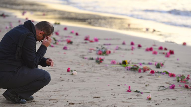 Flowers were scattered on Sydney's Freshwater beach during a vigil for Ms Damond
