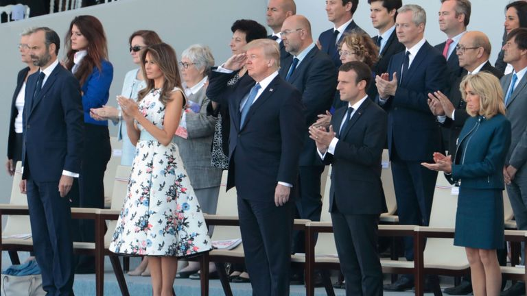 Donald Trump  salutes US troops, flanked by (from L) Melania Trump, French President Emmanuel Macron and his wife Brigitte