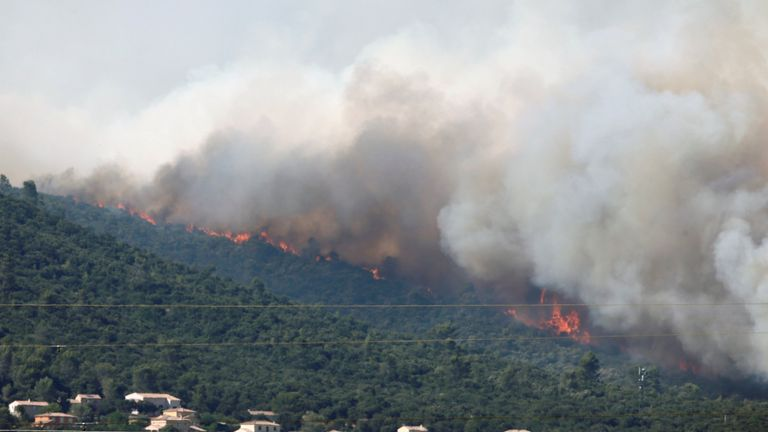 Smoke fills the sky as flames from a wildfire burn trees near Seillons, in the Var department, France