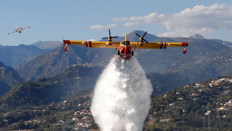 A Canadair firefighting aircraft drops water on a wildfire which burns a forest in Carros near Nice