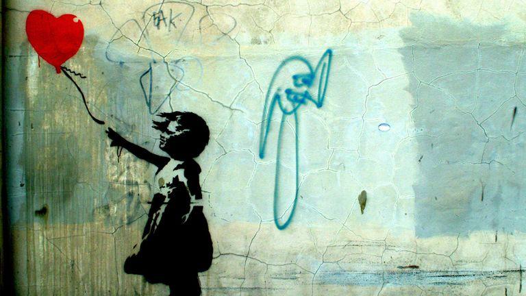 Girl holding a heart balloon. Photograph of Banksy's graffiti street art from 2004