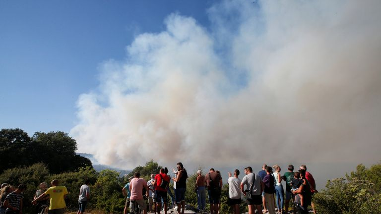People look at smoke that fills the sky from a forest fire near Seillons, in the Var department