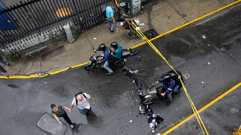 Pedestrians and a motorcyclist pass through a barricade