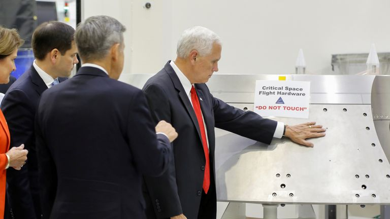 "U.S. Vice President Mike Pence touches a piece of hardware with a warning label ""Do Not Touch"" next to Kennedy Space Center Director Robert Cabana during a tour of the Operations and Checkout Building in Florida July 6, 2017. Picture taken July 6, 2017"