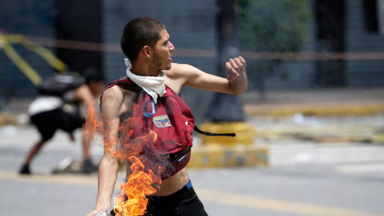 A demonstrator throws a Molotov cocktail