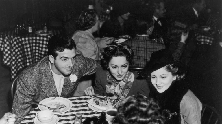 Dame Olivia leans in to hear a conversation with her sister Joan Fontaine and actor John Payne in 1940
