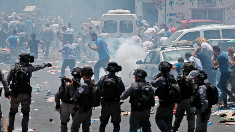 Muslim worshippers run for cover from teargas, fired by Israeli forces