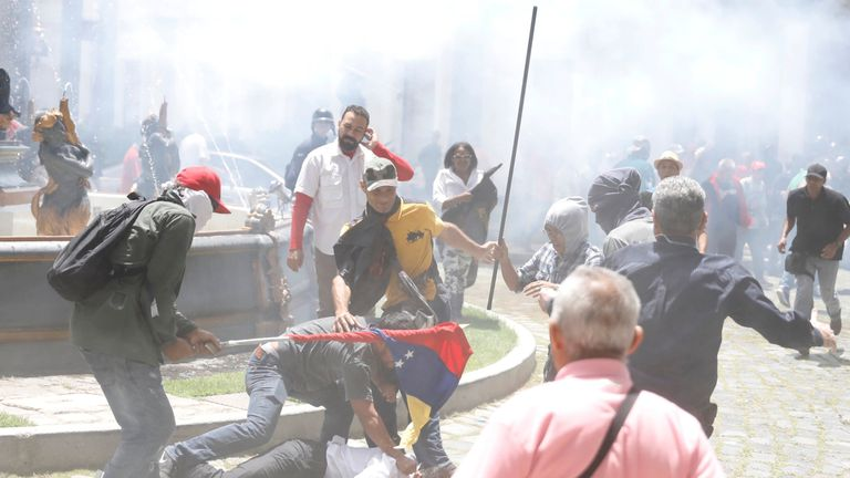 Government supporters attack a person outside Venezuela's opposition-controlled National Assembly