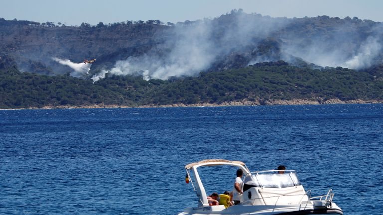 A Canadair firefighting plane drops water to extinguish a forest fire on La Croix-Valmer from Cavalaire-sur-Mer, near Saint-Tropez