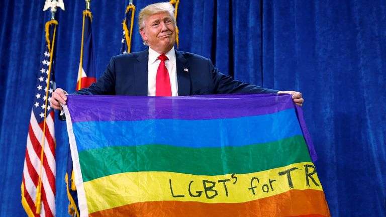 """Republican presidential nominee Donald Trump holds up a rainbow flag with """"LGBTs for TRUMP"""" written on it at a campaign rally in Greeley, Colorado, U.S. October 30, 2016. REUTERS/Carlo Allegri TPX IMAGES OF THE DAY"""