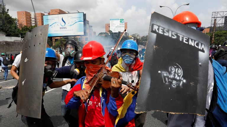 Wuilly Arteaga plays the violin during a protest against the poll