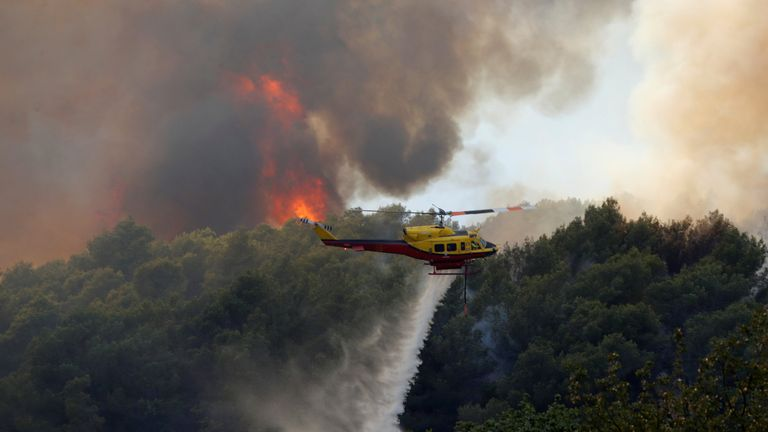 A helicopter drops water as flames and smoke from a burning wildfire fills the sky in Carros, near Nice
