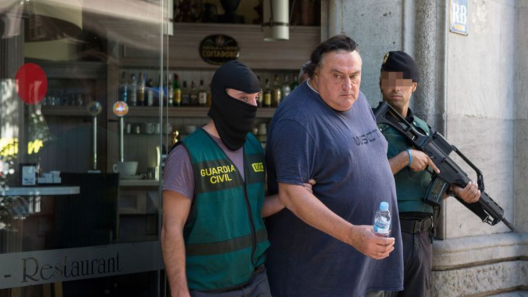 Guardia Civil officers arrest a man after searching a restaurant in Barcelona