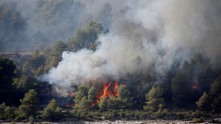Smoke and flames from wildfire burn trees in woods near a river in Peyrolles, in the north of the Bouches-du-Rhone department