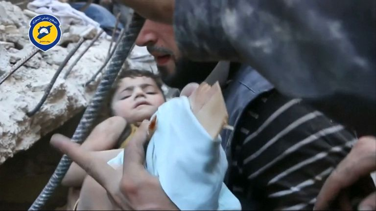 A child is pulled from the rubble of a building destroyed in an airstrike