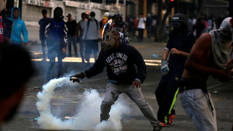 A demonstrator prepares to throw tear gas