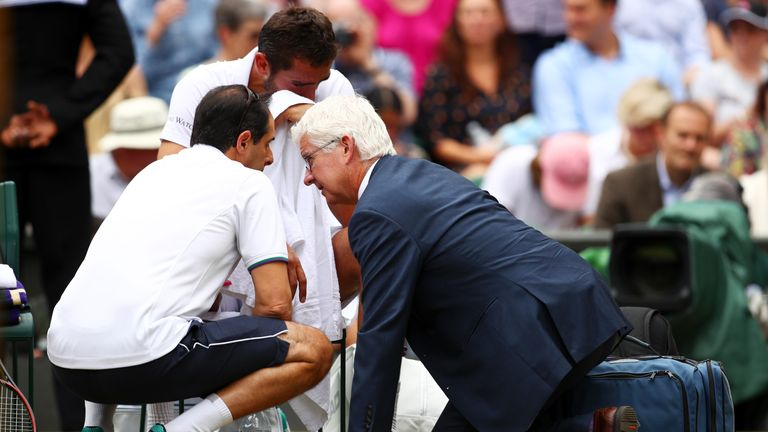 An emotional Marin Cilic of Croatia is given assistance during the Gentlemen's Singles final against Roger Federer