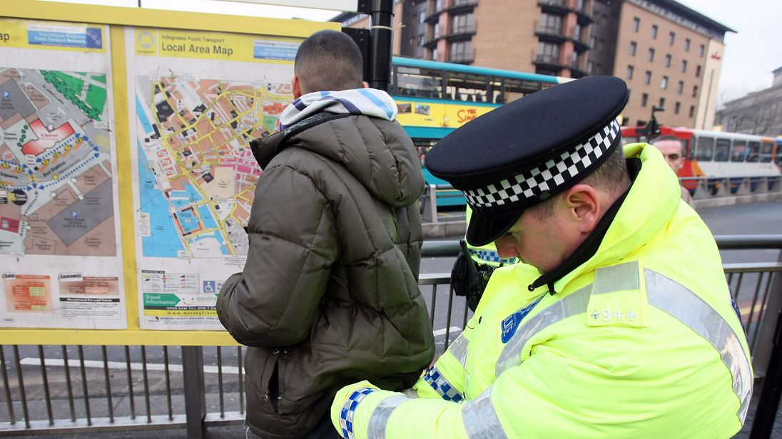 An officer carries out a stop and search in Liverpool