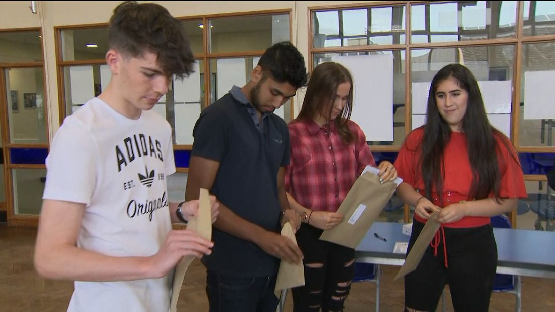 Students open envelopes containing their GCSE results
